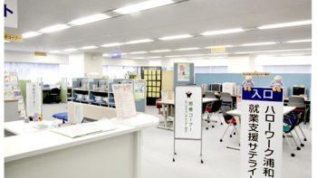 手前に受付のデスク、4人が座れるテーブルが2台、奥にパソコンがある若者コーナー(ヤングキャリアセンター埼玉)の写真。