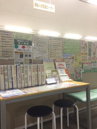 資料が置いてある机と、チラシが貼られている壁が写っている福祉人材就職コーナーの画像。