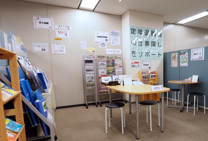 シニア情報ブースの写真で、定年退職後の仕事探しをサポートという大きな張り紙が見える。ブースの中央には椅子とテーブルが複数あり、気になる求人をゆっくり閲覧することができる様子が分かる。