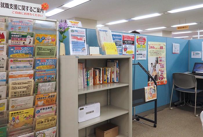 ハローワーク浦和・就業支援サテライト内の雰囲気を伝える写真で、応募書類を作成するためのパソコンブースが設置されている他、就職支援に関するチラシや書籍が配架されており、自由に閲覧できる様子が分かる。