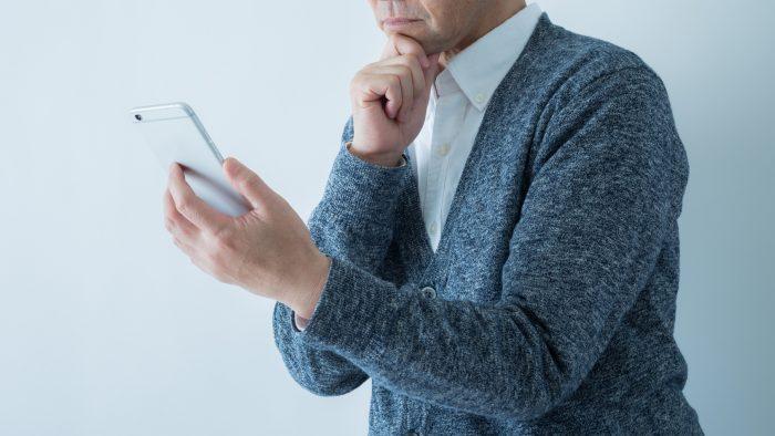 シニア男性がスマートフォンの画面をながめながらもう片方の手を顎に当てて悩んでいる様子