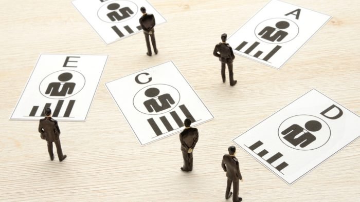 A、B、C、D、Eと書かれたカードが散らばっており、それらを複数のビジネスマンが吟味している様子。