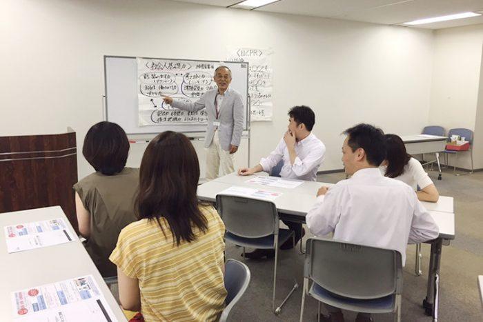セミナー室で1人の講師と、5人の生徒が講義を受けている風景